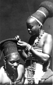 Young Zulu woman braiding hair